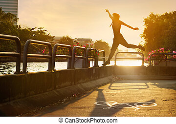 sport women jumping on the bike lane in the sunrise, soft...