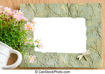 Blank photo frame and pink flower on wooden background save...