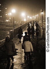 City commuters cross over the bridge in the foggy night
