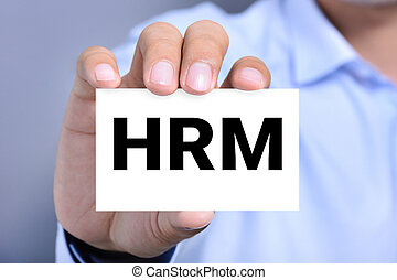 HRM letters or Human Resources Management on the card held...