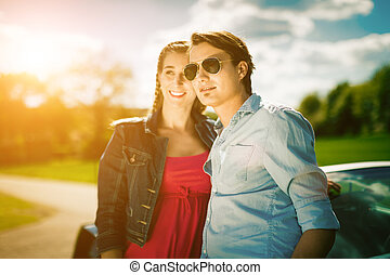 couple with cabriolet car in spring on day trip - Young hip...