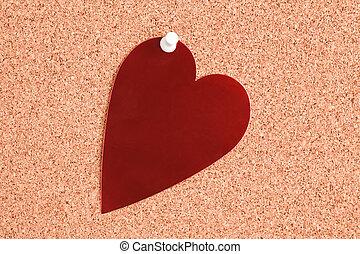 red heart on corkboard