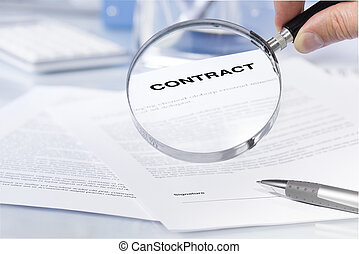 Close-up Of Person's Hand Looking At Contract Through...