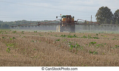 Tractor spray stubble field with herbicide chemicals in...
