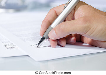 Close-up shot of hand signing a document with a silver pen...