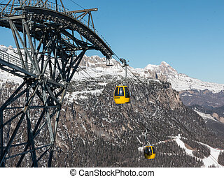 yellow cable car ski lift going up on the mountain top