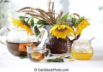 Still-life with tea, honey and sunflowers