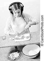 beautiful blond young woman making pizza in headphones -...