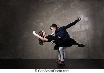 Beautiful couple in the active ballroom dance on dark...