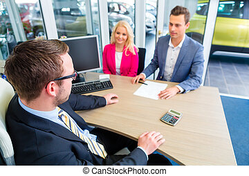 Couple negotiating sale contact for car - Couple buying car...