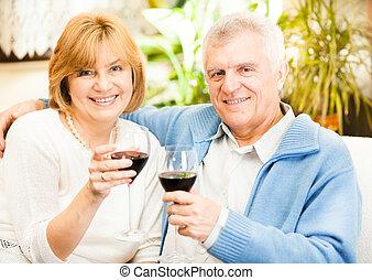 Happy Senior Couple - Happy senior couple toasting their...