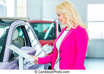 Woman choosing car for buying in dealership