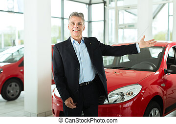 Mature man with auto in car dealership