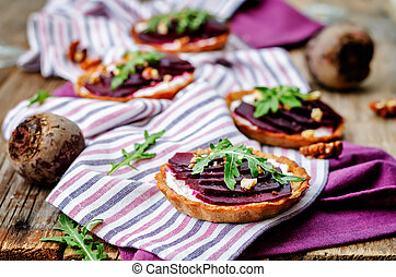 goat cheese beet arugula walnut honey tartlets on a dark...