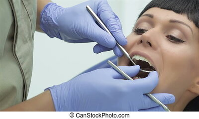Dentist makes the process of treatment of a beautiful young...