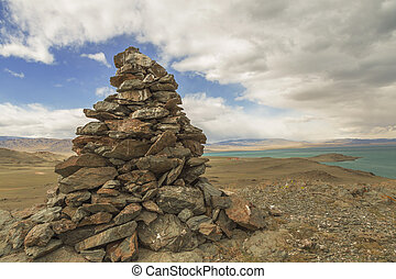 A pile of stones ritual on the lake Uureg Nuur in Mongolia -...