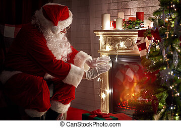 Santa Claus warming his hands at fire fireplace