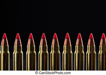 Top croped cartridges ranked with red tip on a black...