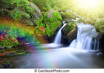 Waterfall on creek with rainbow. National park Sumava-Czech...