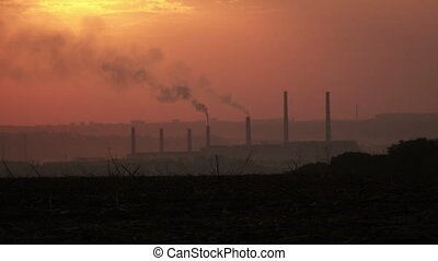 Smoke from pipes at sunset