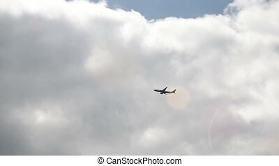Plane flies by on a cloudy sky - A plane flies by on a...