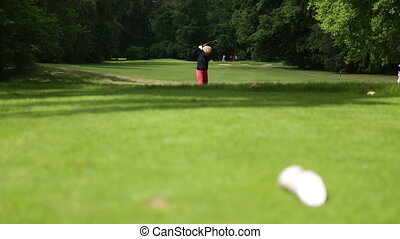 Woman playing a drive at a golf course - A woman is playing...