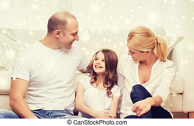 parents and little girl sitting on floor at home
