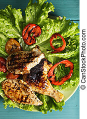 Grilled chicken breasts and leg on lettuce above view -...