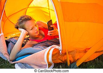 Pretty, young woman camping outdoors, lying in the tent in the morning, using her smart phone