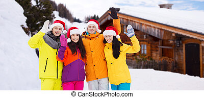 happy friends in santa hats and ski suits outdoors - winter...