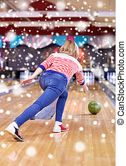 happy young woman throwing ball in bowling club - people,...