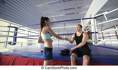 Young girl athlete comes to fitness instructor and takes his hand to shake