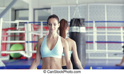 Girl athlete doing exercises with barbell met her fitness instructor
