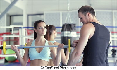 Fitness instructor shows a young girl athlete what muscle group work