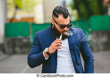 man with a beard smokes electronic cigarette - well dressed...