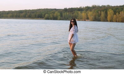 girl walking on the river at sunset