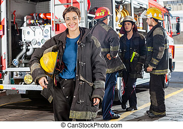 Happy Firewoman With Colleagues Discussing By Truck -...