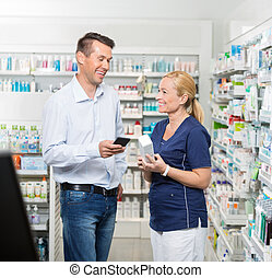 Customer Holding Mobile Phone While Pharmacist Showing Product