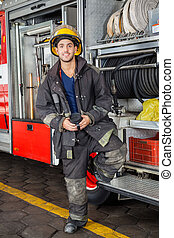 Smiling Fireman Standing By Truck At Fire Station - Full...