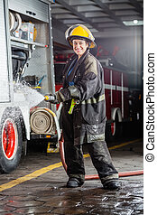 Happy Firewoman Spraying Water During Practice - Portrait of...
