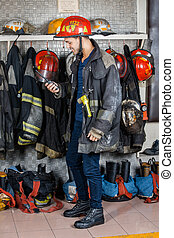 Firefighter Looking At Walkie Talkie In Fire Station - Full...