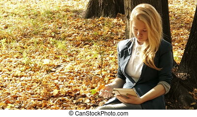 Smiling girl with tablet pc on  autumn