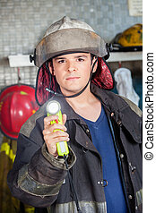 Confident Firefighter Holding Torch At Fire Station -...