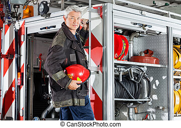 Confident Fireman Standing On Fire Engine - Portrait of...