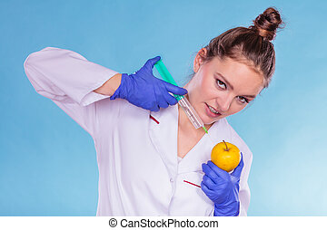 Scientist doctor injecting apple. GM Food. - Scientist...