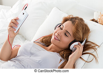 Young beautiful woman laying in her bedroom and listening to music