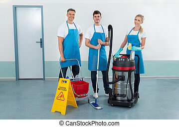 Workers With Cleaning Equipments - Portrait Of Happy Three...