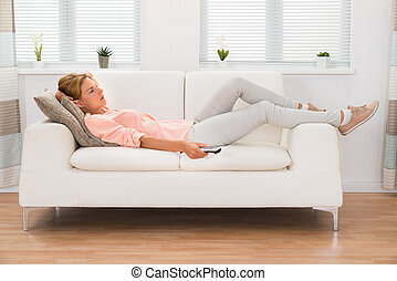 Woman Changing Channel With Remote Control - Young Woman On...