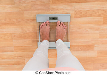 Woman Standing On Weighing Scale - Low Section Of Woman...