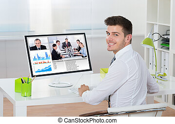 Businessman Videoconferencing On Computer - Young Happy...